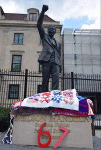 "photo of a statue of Nelson Mandela, with donated hand-made blankets on the base, and the number ""67"""